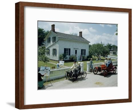People in Costume Park Antique Ford Cars Near Henry Ford's Birthplace-Andrew Brown-Framed Art Print