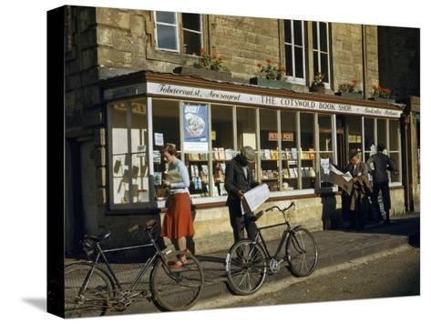 Villagers Read Newspapers Near Bicycles Outside a Book Shop-Melville Grosvenor-Stretched Canvas Print