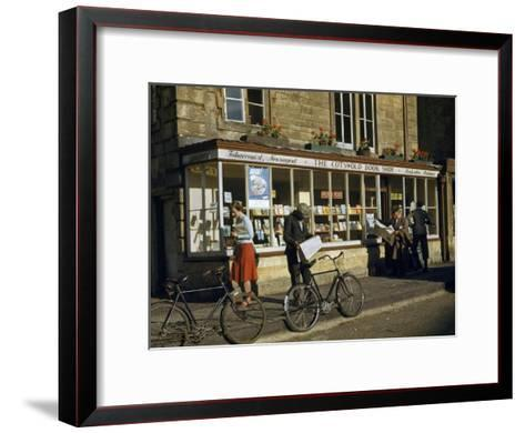 Villagers Read Newspapers Near Bicycles Outside a Book Shop-Melville Grosvenor-Framed Art Print