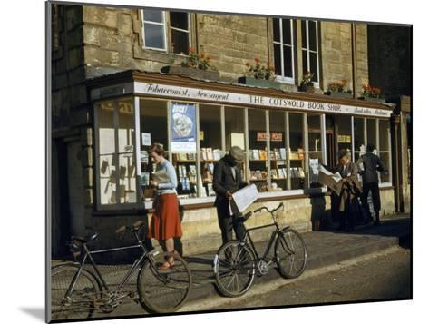 Villagers Read Newspapers Near Bicycles Outside a Book Shop-Melville Grosvenor-Mounted Photographic Print