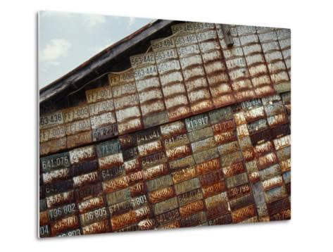 Side of a Building Adorned with Old License Plates-Raymond Gehman-Metal Print