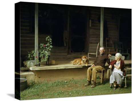 Rural Couple Sits in Chairs on Lawn, Dog Lies on Shady Porch Nearby--Stretched Canvas Print