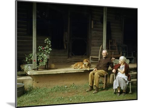 Rural Couple Sits in Chairs on Lawn, Dog Lies on Shady Porch Nearby--Mounted Photographic Print