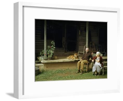 Rural Couple Sits in Chairs on Lawn, Dog Lies on Shady Porch Nearby--Framed Art Print