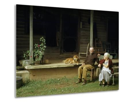 Rural Couple Sits in Chairs on Lawn, Dog Lies on Shady Porch Nearby--Metal Print