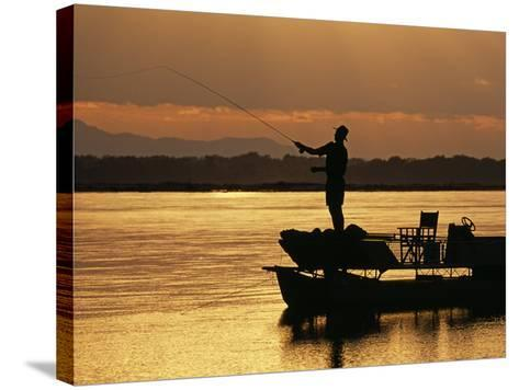 Lower Zambezi National Park, Fly Fishing for Tiger Fish from a Barge on the Zambezi River at Dawn, -John Warburton-lee-Stretched Canvas Print