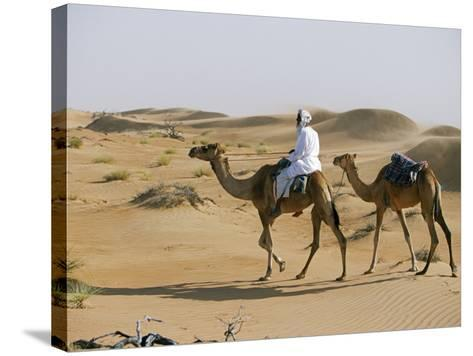 Bedu Rides His Camel Amongst the Sand Dunes in the Desert-John Warburton-lee-Stretched Canvas Print