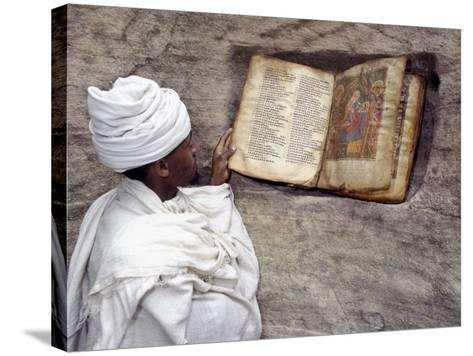 Priest of Ethiopian Orthodox Church Reads Old Bible at Rock-Hewn Church of Yohannes Maequddi-Nigel Pavitt-Stretched Canvas Print