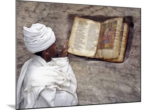 Priest of Ethiopian Orthodox Church Reads Old Bible at Rock-Hewn Church of Yohannes Maequddi-Nigel Pavitt-Mounted Photographic Print