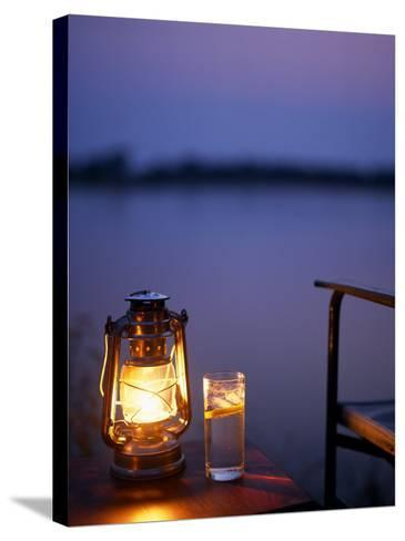 Gin and Tonic by the Light of Hurricane Lamp, Looking Out over the Zambezi River, Zambia-John Warburton-lee-Stretched Canvas Print