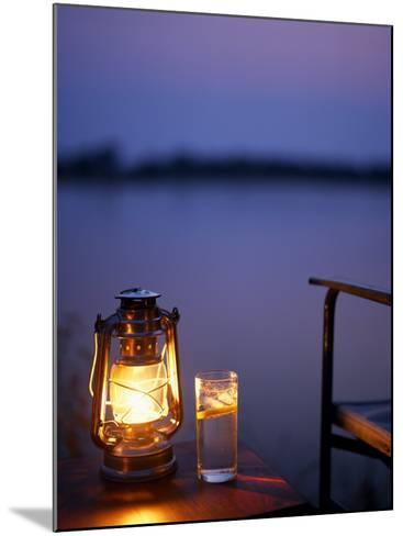 Gin and Tonic by the Light of Hurricane Lamp, Looking Out over the Zambezi River, Zambia-John Warburton-lee-Mounted Photographic Print
