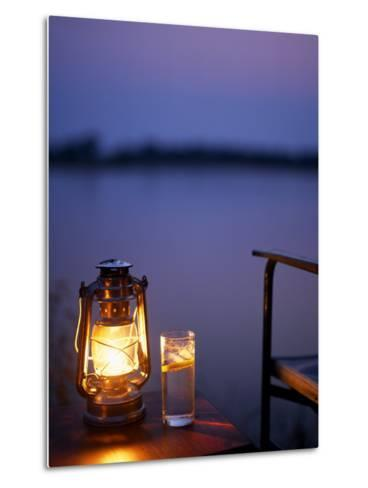 Gin and Tonic by the Light of Hurricane Lamp, Looking Out over the Zambezi River, Zambia-John Warburton-lee-Metal Print