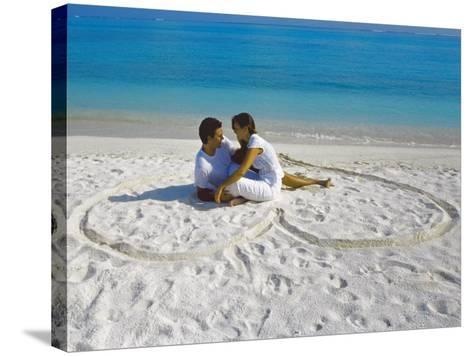 Young Couple on Beach Sitting in a Heart Shaped Imprint on the Sand, Maldives, Indian Ocean, Asia-Sakis Papadopoulos-Stretched Canvas Print