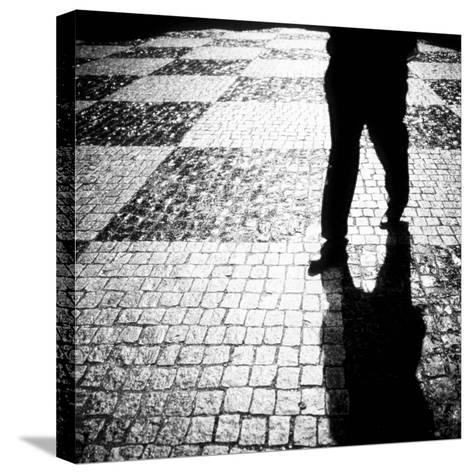 Silhouette of Mans Legs Walking on Cobblestone Street at Night-Elke Hesser-Stretched Canvas Print