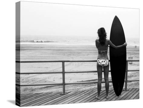 Model with Black Surfboard Standing on Boardwalk and Watching Wave on Beach-Theodore Beowulf Sheehan-Stretched Canvas Print