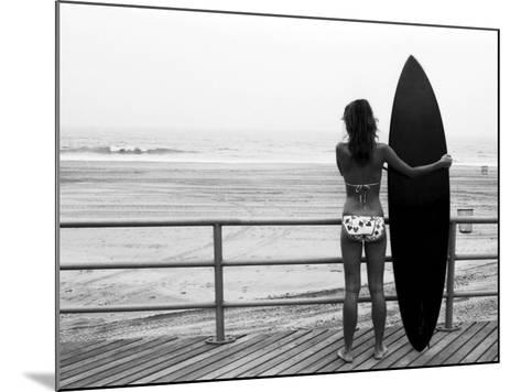 Model with Black Surfboard Standing on Boardwalk and Watching Wave on Beach-Theodore Beowulf Sheehan-Mounted Photographic Print