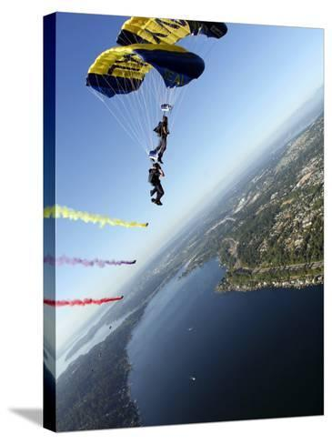 Members of US Navy Parachute Team, the Leap Frogs, Perform Bi-Plane with Parachutes Above Seattle--Stretched Canvas Print