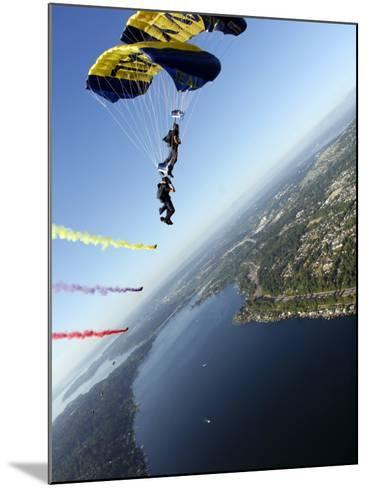 Members of US Navy Parachute Team, the Leap Frogs, Perform Bi-Plane with Parachutes Above Seattle--Mounted Photographic Print