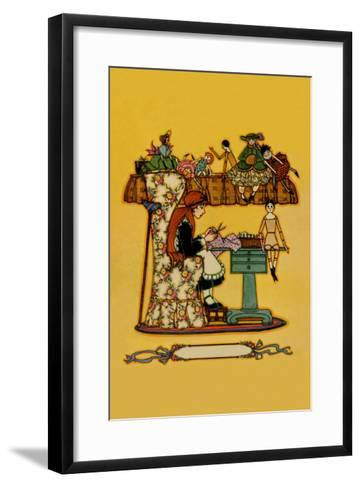 Young Girl Cuts Patterns For a Collection of Dolls--Framed Art Print