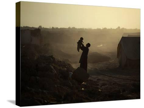Displaced Man Holds His Baby Next to His Tent in Jalozai Refugee Camp Near Peshawar, Pakistan--Stretched Canvas Print
