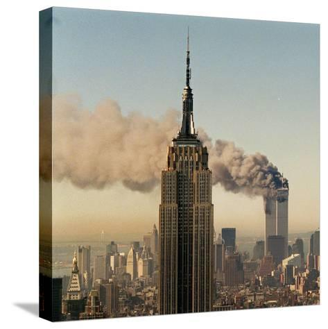 Twin Towers of the World Trade Center Burn Behind the Empire State Buildiing, September 11, 2001--Stretched Canvas Print