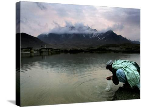 Afghan Man Washes His Face in the River before Going to Evening Prayers--Stretched Canvas Print
