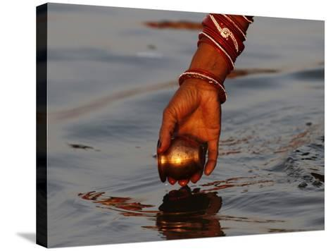 Woman Praying on the Banks of the River Ganges Fills Water into a Copper Vessel for a Ritual--Stretched Canvas Print