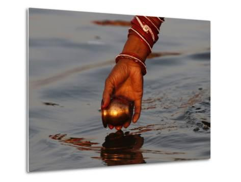 Woman Praying on the Banks of the River Ganges Fills Water into a Copper Vessel for a Ritual--Metal Print