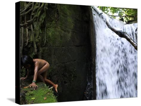 Child from the Ache Indigenous Group Plays Near a Waterfall in Cerro Moroti, Paraguay--Stretched Canvas Print