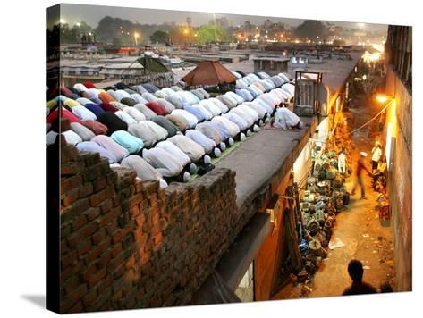 Indian Muslims During Friday Evening Prayers on the Rooftop of a Building over an Auto Parts Market--Stretched Canvas Print