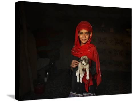 Girl Holds a Puppy as the Sun Sets over Kabul's Impoverished Teppe Maranjan Neighborhood--Stretched Canvas Print