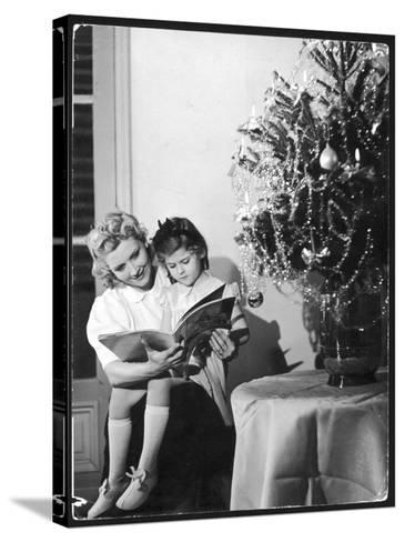 A Little Girl Sits on Her Mother's Knee and Reads a Book Beside the Christmas Tree--Stretched Canvas Print