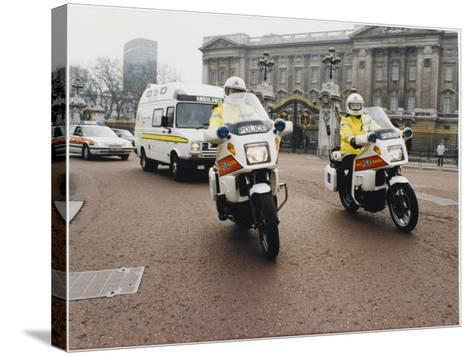 Metropolitan Police Motorcyclists Esccorting an Ambulance Past Buckingham Palace in London--Stretched Canvas Print