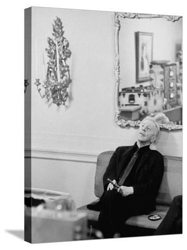 Pianist Artur Rubinstein Sitting on Couch and Holding Cigar During Restful Moment--Stretched Canvas Print