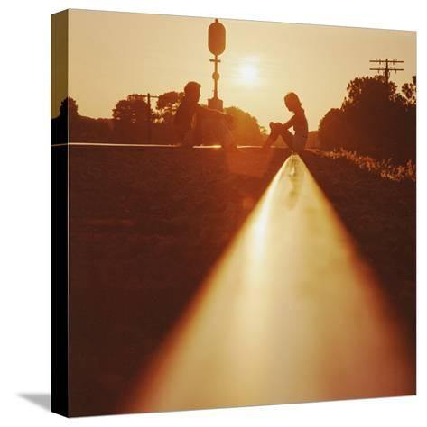 Silhouette of Couple Sitting on Railroad Tracks at Sunset-Dennis Hallinan-Stretched Canvas Print