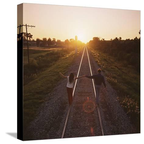 Couple Walking on Railroad Tracks Holding Hands-Dennis Hallinan-Stretched Canvas Print