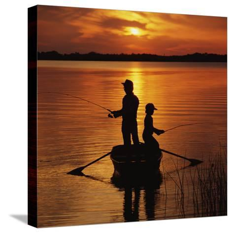 Silhouette of Father and Son Fishing at Sunset-Dennis Hallinan-Stretched Canvas Print