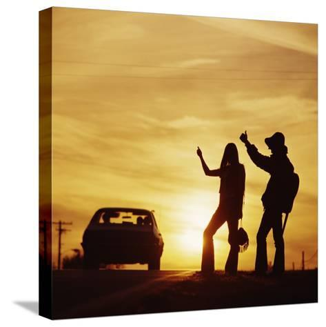 Silhouetted Couple Hitchhiking on Roadside-Dennis Hallinan-Stretched Canvas Print