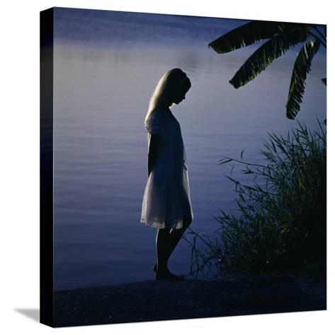 Silhouette of woman standing near a lake-Dennis Hallinan-Stretched Canvas Print