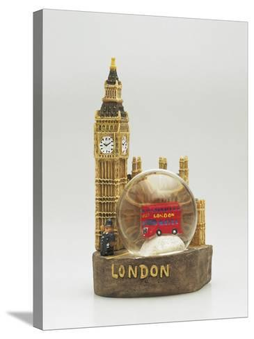 Close-Up of a Toy Bus in a Snow Globe in Front of a Figurine of a Clock Tower--Stretched Canvas Print
