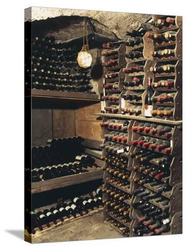 Wine Bottles on a Rack in a Wine Cellar-G^ Cigolini-Stretched Canvas Print