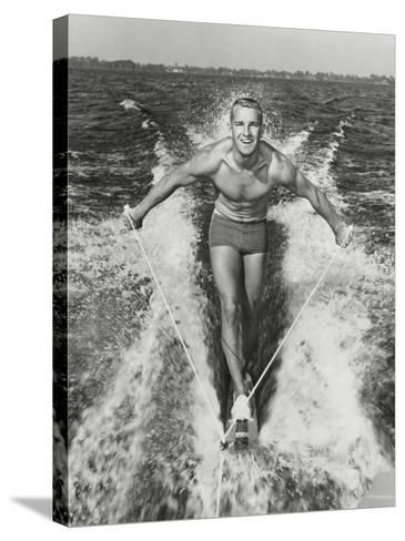 Happy Young Man Waterskiing-Dennis Hallinan-Stretched Canvas Print