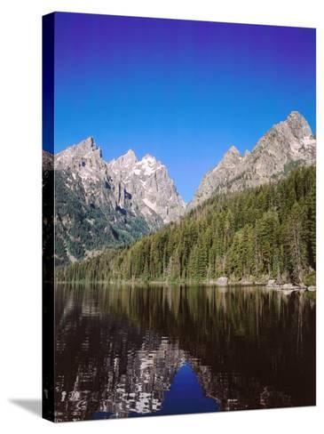 View of Grand Teton and Mount Owen Reflected in Calm Waters of Jenny Lake-Jeff Foott-Stretched Canvas Print