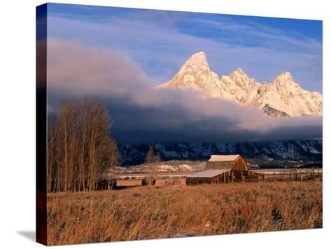 View of Historic Old Barn and Snow-Covered Teton Mountain Range-Jeff Foott-Stretched Canvas Print