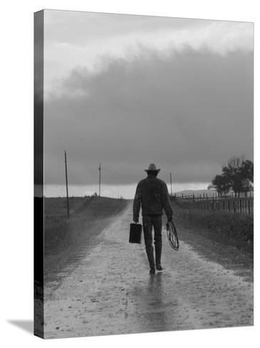 Silhouette of Cowboy Walking on Empty Road--Stretched Canvas Print