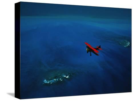 An Airplane Flying over Water-David Doubilet-Stretched Canvas Print