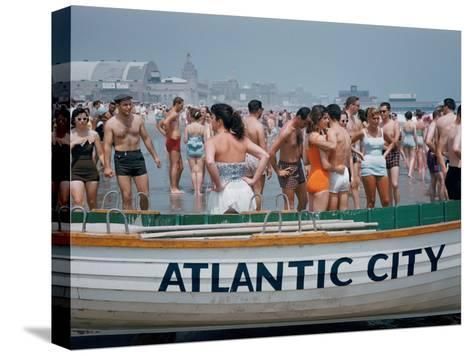 Throngs of Swimmers Stroll Behind a Wooden Lifeboat on the Beach-Volkmar K^ Wentzel-Stretched Canvas Print