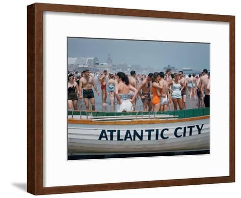 Throngs of Swimmers Stroll Behind a Wooden Lifeboat on the Beach-Volkmar K^ Wentzel-Framed Art Print