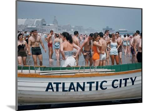 Throngs of Swimmers Stroll Behind a Wooden Lifeboat on the Beach-Volkmar K^ Wentzel-Mounted Photographic Print