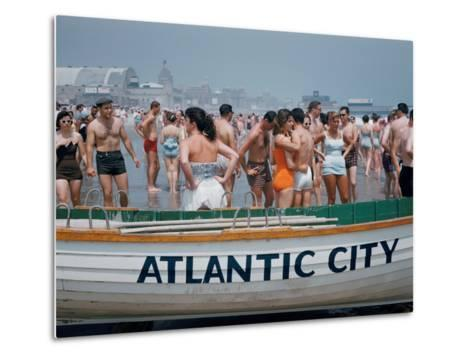 Throngs of Swimmers Stroll Behind a Wooden Lifeboat on the Beach-Volkmar K^ Wentzel-Metal Print